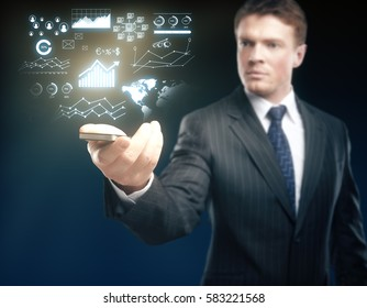 Blurry handsome businessman holding smartphone with abstract business chart holograms. Technology concept