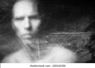 Blurry human face behind dusty scratched glass