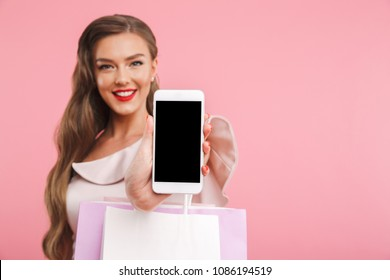 Blurry image of adorable brunette woman smiling and demonstrating copyspace screen of smartphone while holding shopping bags isolated over pink background