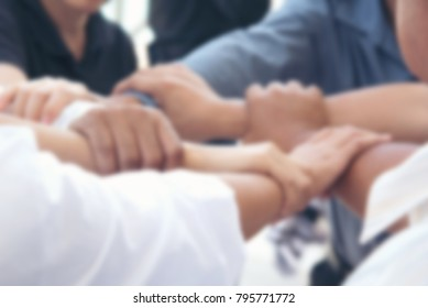 Blurry image for background. Seven hands hold together like square shape, mean be in harmony,agreement,power and friendship in business or team.