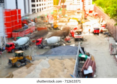 Blurry image of construction worker on site and machinery on street