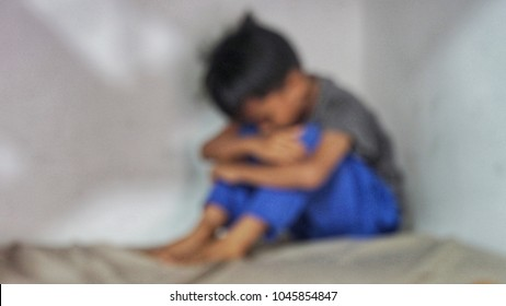 Blurry image of a depressed boy sitting at the corner of a house. Domestic crime concept. Abuse child.