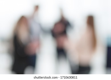 blurry image of employees standing in the office.