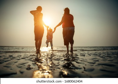 Blurry image of family couple with small baby against sunset on the sea. Family idyll, silhouettes of husband, wife and small child on the background of the ocean in the sunlight.