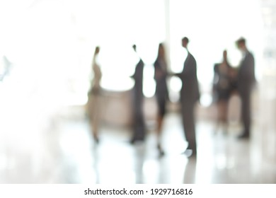 blurry image of a group of business people standing in the office lobby.
