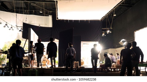 Blurry image of making movie video in big production studio and film crew team shooting or recording by professional digital camera and lighting set equipment.