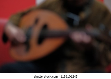 Blurry image of man playing qanbus or gambus. Gambus is arabic music instrument shape like the guitar with rounded body.