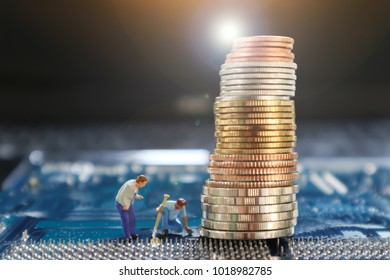 Blurry image of miniature mini figures digging coins on printed circuit computer mother board dark background of notbook. using as background business concept. bitcoin concept.