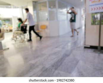 The blurry image of Nursing Assistant  Pushing a wheelchair with the patient sitting.  to the hospital location