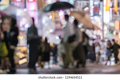 Blurry image of people with umbrella in Tokyo street.