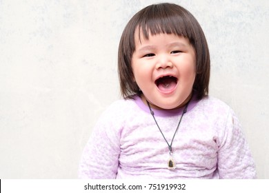 Blurry image of Portrait Little Asian girl, smiling face, wearing a purple sweater, sitting smiling, good mood because of cold weather.concept welcome winter
