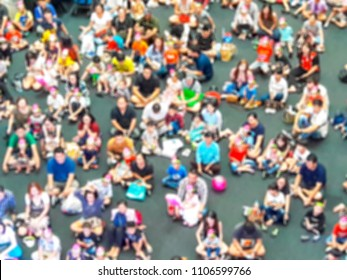 Blurry images of many people sit and watch something.
