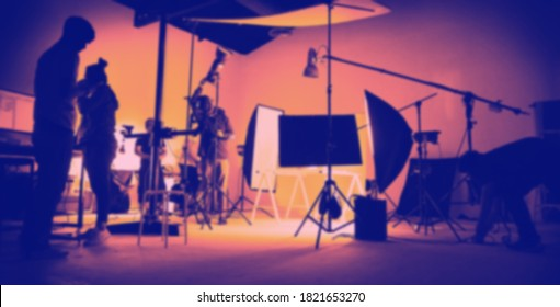 Blurry images Two tone high contrast style of behind the scene of photo shooting production set up in the big studio. Professional crew team working and camera equipment in silhouette.