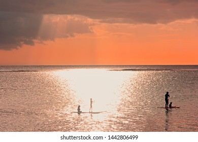 Blurry image.Soft focused sunset scene on coming thunderstorm background. Blurry family silhouettes at sunset on ocean.A father with three children are paddling on two boards.Family supping.