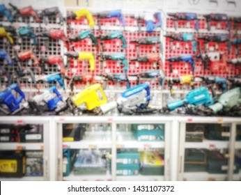 Blurry industrial tools and electric drill in hardware shop as abstract background
