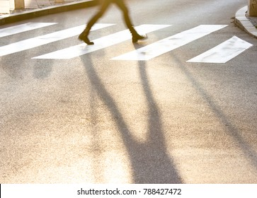 Blurry legs and shadow of a teenage girl crossing the small city street at sunset in a hurry