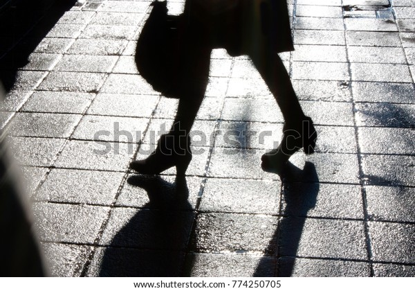 Blurry legs of a young woman walking on the city sidewalk in the night in black and white