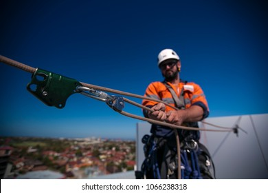 Blurry male rope access industry worker wearing full body safety harness, white hard hat, using advantage mechanical three two one pulley system lift items up on construction building site in Sydney