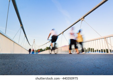 Blurry motion image of people walking and riding a bike on a pedestrian bridge
