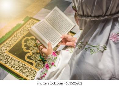 Blurry muslim girl read her koran.Islamic education inside white mosque.