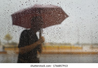 Blurry of the old man with umbrella during hard rainfall/Dramatic scene of rainy season in Southeast Asia).Selective focus and shallow depth of field composition.