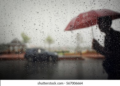 Blurry of the old man with umbrella during hard rainfall( Dramatic scene in Southeast Asia).Selective focus and shallow depth of field composition,color toned.