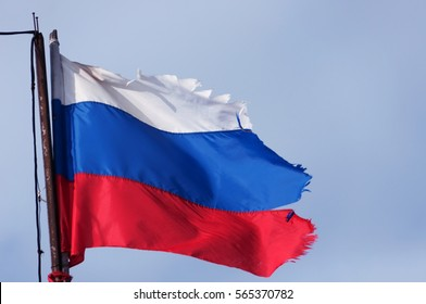 blurry Old torn Russian flag on the rusty flagpole