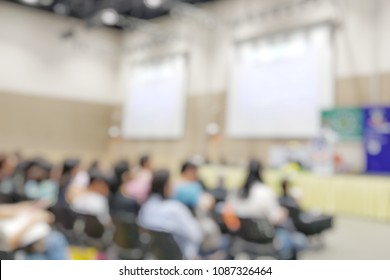 Blurry open house day in meeting hall at campus for middle school students.Blur abstract background teacher in front of classroom for meet the parent day with projector screen.
