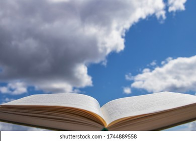 Blurry pages of an open book, on a background of blue sky with clouds.