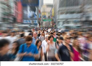 blurry people across a road in shibuya japan