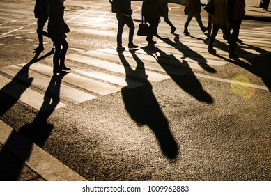 Blurry people crossing the street on zebra crossing and making shadows