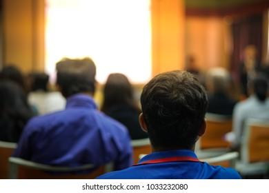 Blurry people in seminar room.