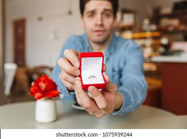 Blurry photo of excited man sitting at table in cafe and proposing to his girlfriend while demonstrating box with engagement ring at camera