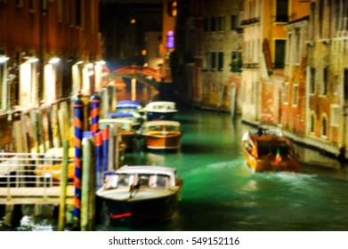 Blurry photo of small canal at night. Venice (Italy)