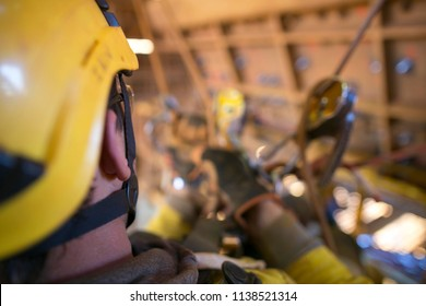 Blurry pic of two descender hanging on safety harness loop while rope access industrial worker commencing maneuvering releasing rope to the right side  construction mine site, Perth, Australia