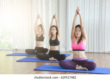 Blurry Picture Group of Young Women Doing Meditation While Practicing Yoga and Workouts in Workouts Class - Sport and Lifestyle Concept