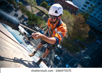 Blurry picture of rope access industry worker wearing a white hard hat using his hand holding back up fall arrest safety device, abseiling down construction building site in Sydney city , Australia