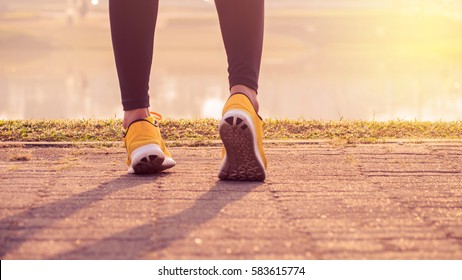 blurry picture runner woman feet running on road on shoe. Female fitness model sunrise jog workout. Sports healthy lifestyle concept.