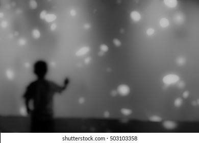 Blurry picture of silhouette children in front of aquarium (Jellyfish tank) - Education concept background - Black and white