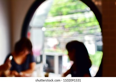 Blurry picture of two women talkative and relaxing or meeting about business at coffee shop, two Asian female in black dress sit at coffee shop inside circle glass window, abstract people background