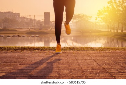 blurry picture young fitness woman runner stretching legs before run. Sports healthy lifestyle concept.