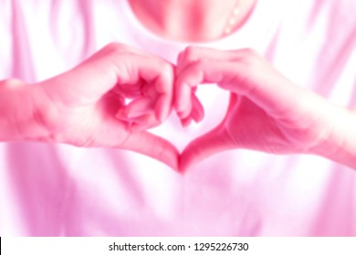 Blurry pink tone image of a person join two hands to be a heart to gesture of love; hand signs of love.