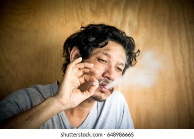 Blurry portrait of man smoking cigarette,Asian man,Addiction, Unhealthy