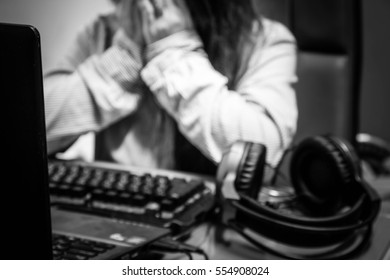 Blurry portrait sad woman using laptop and headphones in room,Black and white