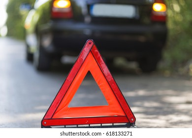 Blurry pose of a  car with a breakdown alongside the road. Focus on the red sign