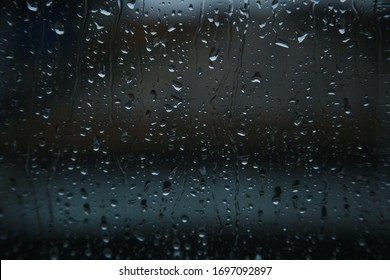 Blurry rain drops on window glasses surface with cloudy background. Dramatic background concept