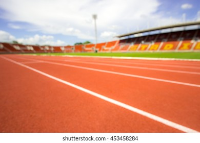 blurry red running track on the athletic stadium, out of focus .
