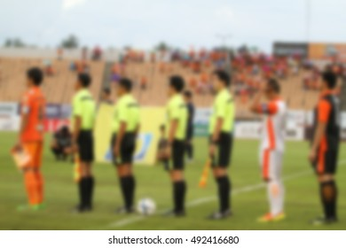blurry referee with captain team and opponent team players on football stadium