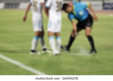 blurry Referee  marks kick off positions with a Vanishing spray