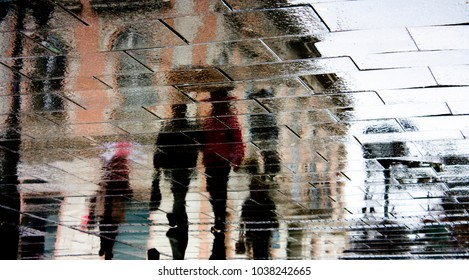 Blurry reflection shadow of people walking the city street patterned sidewalk on a rainy day